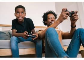 父子俩在家里一起玩电子游戏_9242081