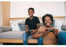 父子俩在家里一起玩电子游戏_9809298