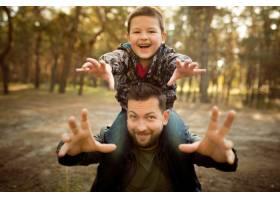 父子俩在秋林里漫步游玩看起来又开心又真_11032762
