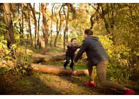 父子俩在秋林里漫步游玩看起来又开心又真_11032766
