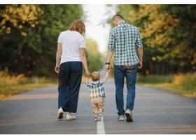 父母抱着他们的小儿子走在路上_8316293