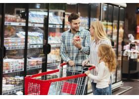 超市里推着购物车的幸福家庭_6729772