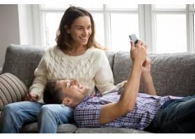 男子向女子展示在沙发上放松的新手机应用程_3953858