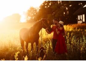 迷人的年轻夫妇牵着一匹棕马站在一座乡间小_2914011