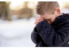 男孩闭着眼睛站着祈祷_10834294