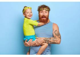 留着胡子的年轻父亲戴着护目镜穿着条纹背_11933302