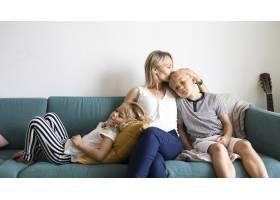 金发妈妈亲吻儿子的头和女儿在沙发上放松_13307309