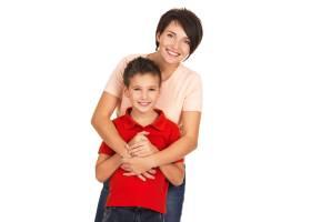白色墙壁上一位幸福的年轻母亲和8岁的儿子_11993989