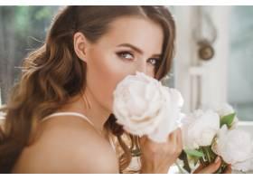 阳光明媚的早晨年轻的新娘手持一束牡丹放_2612757