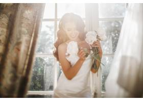 阳光明媚的早晨年轻的新娘手持一束牡丹放_2612764