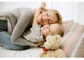 阳光明媚的早晨年轻的母亲和她的小女儿在_10521424