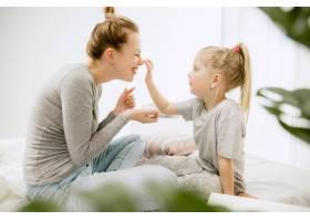 阳光明媚的早晨年轻的母亲和她的小女儿在_10521439