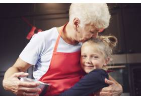 祖母亲吻和拥抱她的孙女_11728102