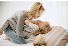阳光明媚的早晨年轻的母亲和她的小女儿在_13457512