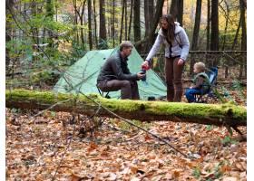 秋天全家在树木和树叶环绕的森林里搭帐篷_10944751