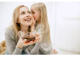 阳光明媚的早晨年轻的母亲和她的小女儿在_13457522