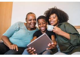 非裔美国奶奶和母子在家中用数字平板自拍的_13101245