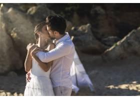 美丽的高加索夫妇在海滩上接吻_11342982