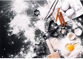 黑色的桌子上摆满了面粉和鸡蛋上面有圣诞_984086