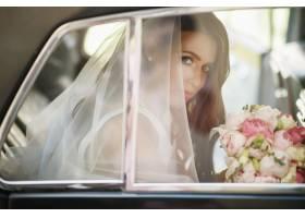 美女新娘坐在复古车里捧着结婚花束玩得开心_2612756
