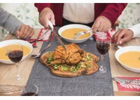 老人在节日餐桌上切烤鸡_3319340
