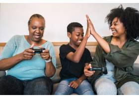 非裔美国祖母和母子在家中一起玩电子游戏的_10104271