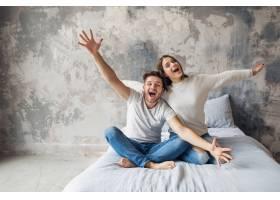 笑容满面的年轻夫妇穿着休闲装坐在家里的床_10274372