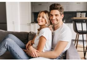 面带微笑的一对迷人的情侣坐在沙发上拥抱着_12152263