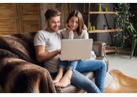 笑容满面的年轻夫妇穿着休闲装坐在家里的沙_9630875
