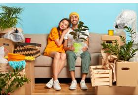 面带微笑的年轻夫妇坐在被箱子包围的沙发上_12608465