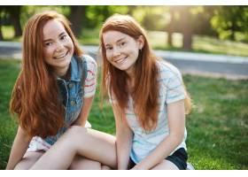红头发长雀斑的欧洲姐妹坐在绿草如茵的草_13516529