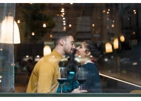 餐馆里幸福的男人和女人在一杯葡萄酒旁_3607932