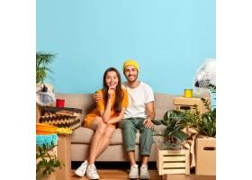 高兴的年轻夫妇坐在被箱子包围的沙发上_12608940