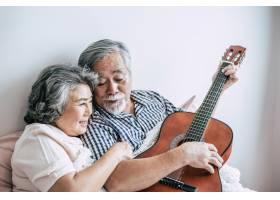 高年级夫妇在卧室里弹着原声吉他放松_4107925