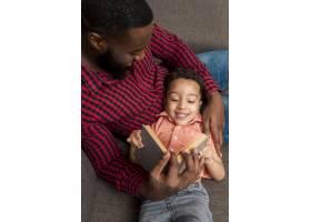 黑人父亲和可爱的儿子坐在沙发上看书_4130677