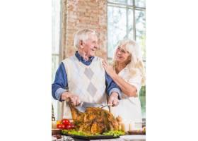 老年男子在妇女旁边的餐桌上切烤鸡_3187349