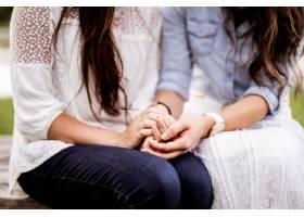 背景模糊的女性夫妇手牵手的特写镜头_13500422
