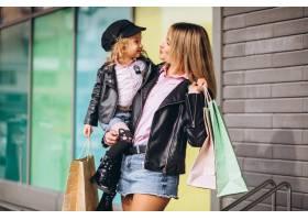 母亲和她可爱的小女儿提着购物袋_6214089