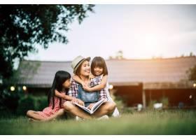 母亲在自家花园给两个小女儿讲故事_2524868