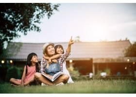 母亲在自家花园给两个小女儿讲故事_2524869