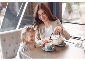母亲带着女儿坐在咖啡馆里_7724951
