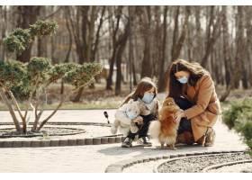 母亲带着女儿戴着口罩走在外面_7710657
