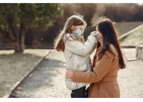 母亲带着女儿戴着口罩走在外面_7727229