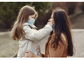 母亲带着女儿戴着口罩走在外面_7727230