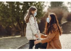 母亲带着女儿戴着口罩走在外面_7727234