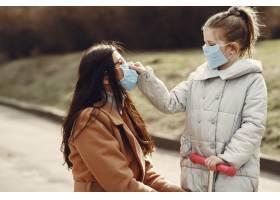 母亲带着女儿戴着口罩走在外面_7727242