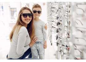 母亲带着年幼的儿子在眼镜店里_5011135