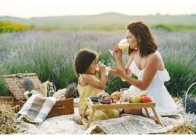 母亲带着年幼的女儿在薰衣草地里美丽的女_10065273