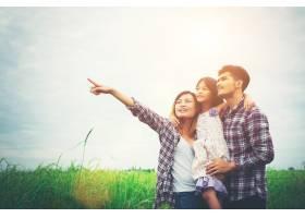 母亲父亲和孩子的一家人在草地上父亲背_1025879