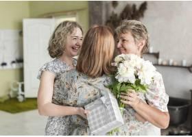 母女俩在家里抱着礼物和花束拥抱他们的祖母_5061063
